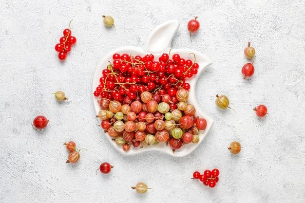 Grosellas dulces orgánicas frescas y grosellas rojas en tazones