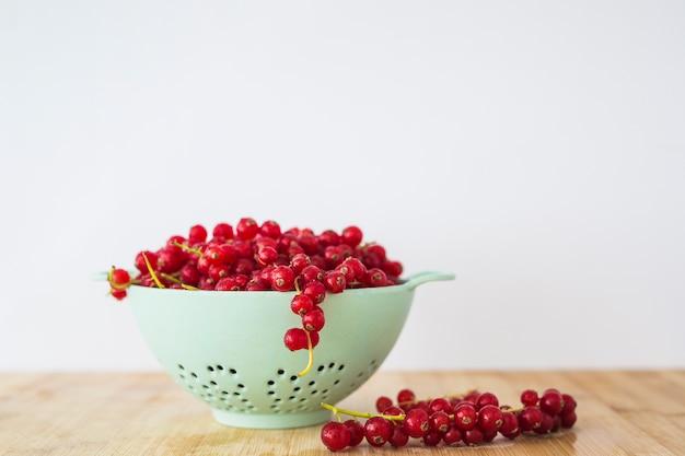 Grosellas rojas en colador en mesa de madera sobre fondo blanco