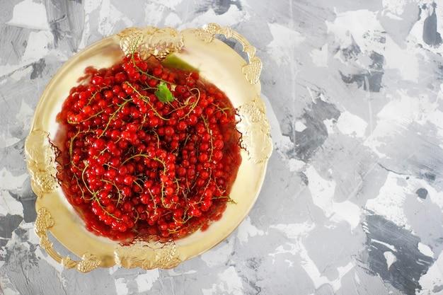 Grosellas rojas frescas en placa de oro
