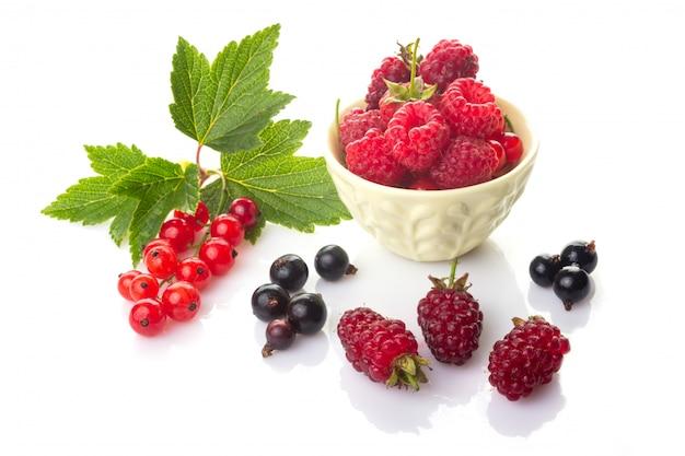Grosellas rojas y negras con hojas verdes, frambuesas en un tazón y loganberry