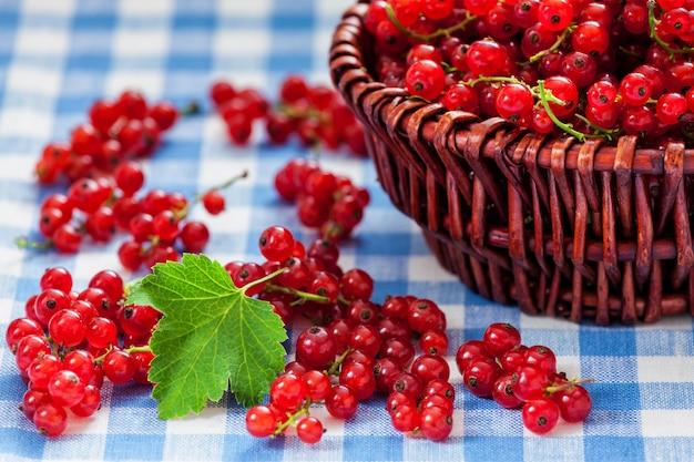 Grosellas rojas en un recipiente de mimbre sobre la mesa