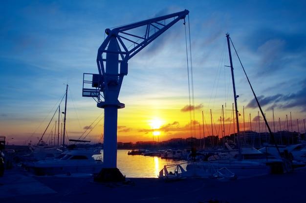 Grúa de barcos al atardecer en el puerto deportivo de salou