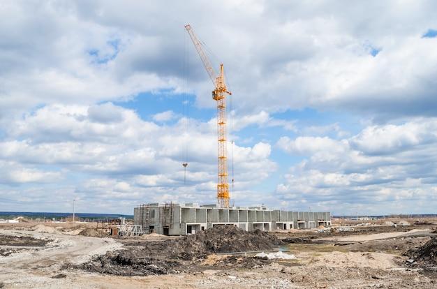 Grúa de construcción amarilla operando en cielo azul y nubes blancas
