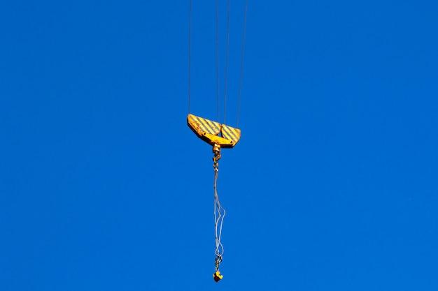 Grúa de construcción y gancho de grúa. concepto de operación y elevación de carga, fondo de cielo azul