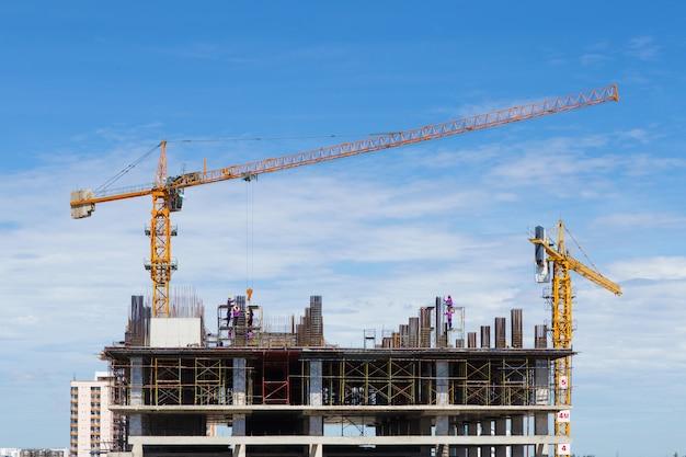Grúa de construcción y trabajador de la industria de la construcción con cielo azul