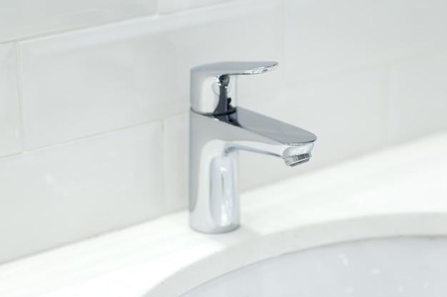 Grúa cromada en el lavabo de cerámica en el baño de cerca