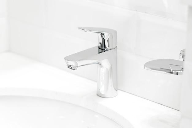 Grúa de cromo en el lavabo de cerámica en el baño de cerca