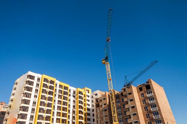 Grúa y edificio de gran altura en construcción contra el cielo azul. fondo de arquitectura moderna