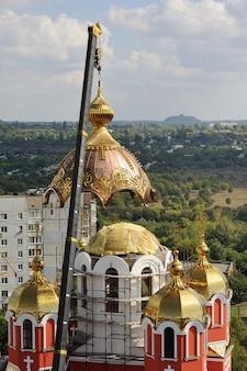 Una grúa levanta la cúpula dorada de la iglesia ortodoxa. construcción y reconstrucción de la iglesia.