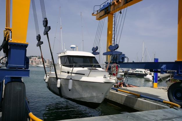 Grúa de muelle elevando un barco de pesca