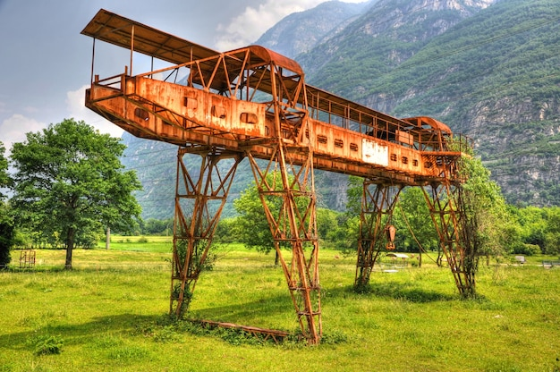 Grúa pórtico oxidada en el campo verde con montañas