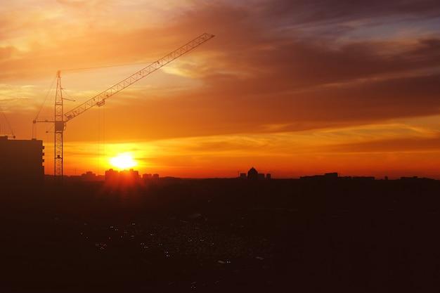 Grúa torre, estacionamiento y autos en la distancia durante la ciudad de la puesta del sol.