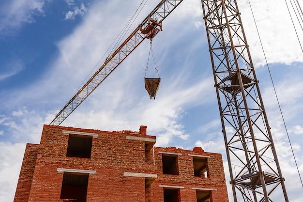 La grúa torre trabaja en el sitio de construcción cerca de la casa de ladrillo