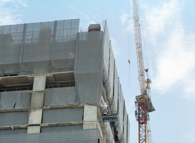 Las grúas de construcción y los edificios de construcción están envueltos en una lona a prueba de polvo para garantizar la seguridad.