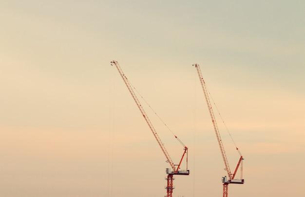Grúas de construcción en el fondo del cielo al atardecer.
