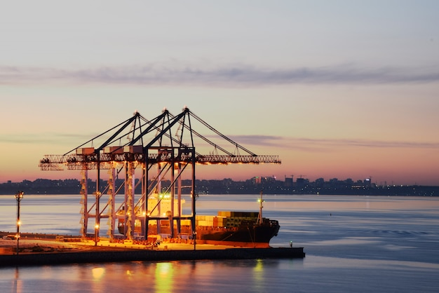 Grúas portuarias en el puerto nocturno. entrega de mercancías por mar.