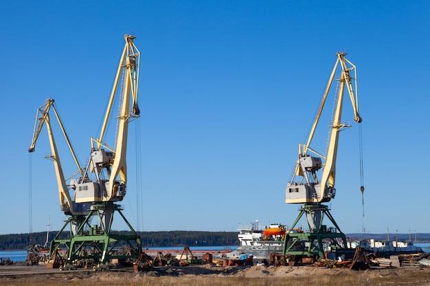 Grúas en el puerto de maquinaria y montacargas para cargar y descargar palets en un día soleado de verano