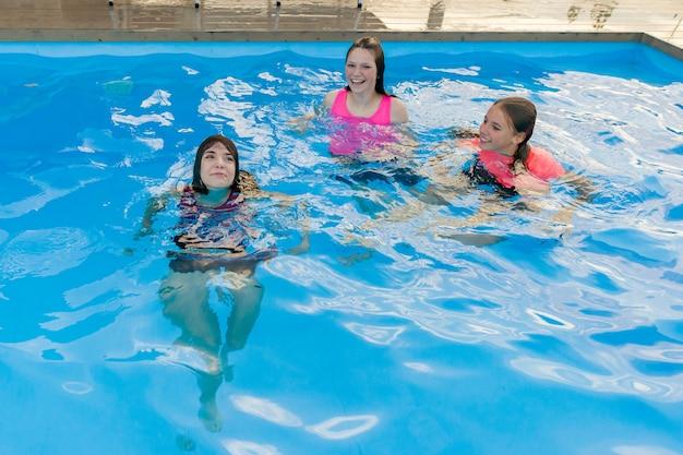 Grupo de 3 novias adolescentes divirtiéndose en la piscina.