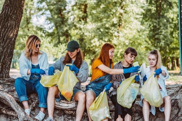 Grupo de activistas amigos recogiendo residuos plásticos en el parque. conservación del medio ambiente.