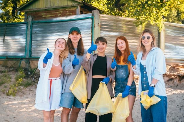 Grupo de activistas amigos recogiendo residuos plásticos en la playa. los chicos muestran el pulgar hacia arriba.