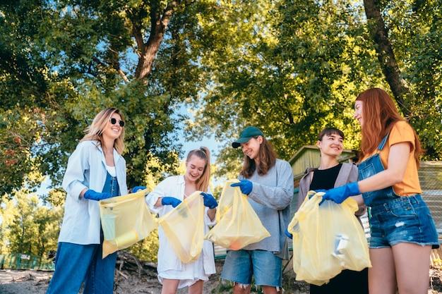 Grupo de activistas amigos recogiendo residuos plásticos en la playa. conservación del medio ambiente.