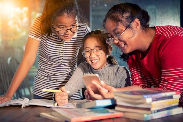 Grupo de adolescente asiático leyendo el mensaje en el teléfono inteligente