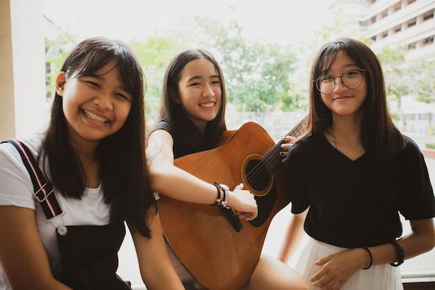 Grupo de adolescente asiático de pie al aire libre manejando la guitarra española