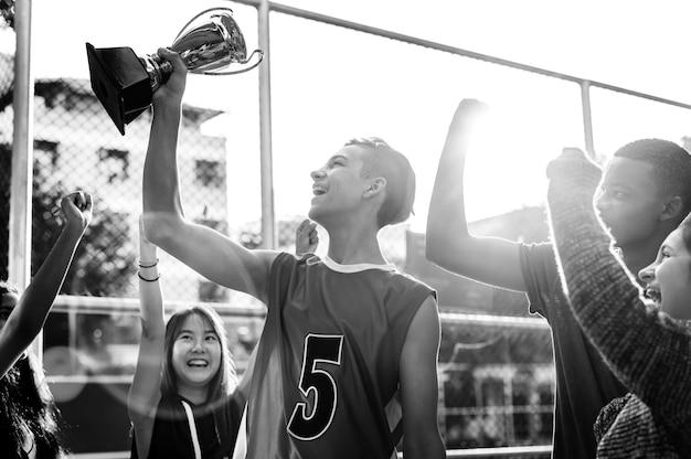 Grupo de adolescentes animando con la victoria de trofeo y el concepto de trabajo en equipo
