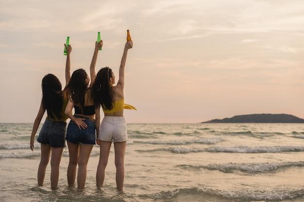 Grupo de adolescentes asiáticas con fiesta celebrando en la playa
