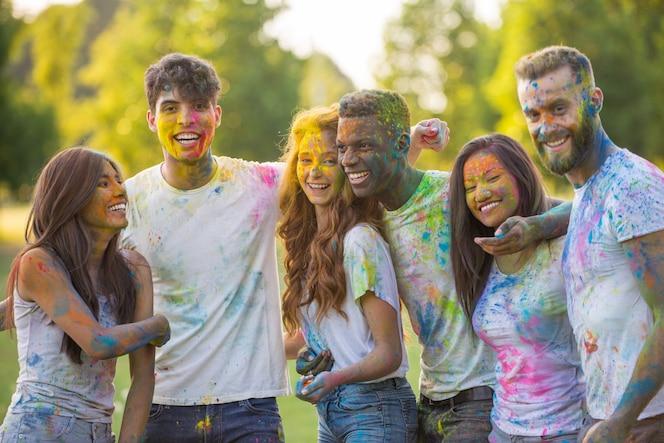 Grupo de adolescentes jugando con colores en el festival holi, en un parque