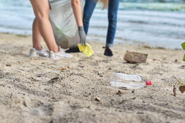 Grupo de adolescentes en la orilla del río recogiendo basura plástica en bolsas. concepto de protección del medio ambiente, juventud, voluntariado, caridad y ecología