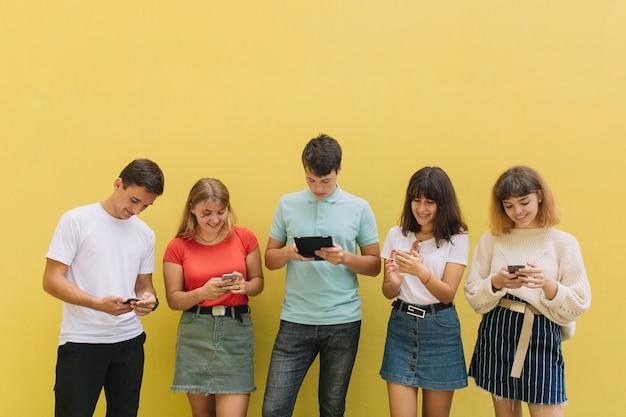 Grupo de adolescentes que usan sus teléfonos móviles y tabletas sobre un fondo amarillo.