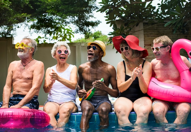 Grupo de adultos mayores diversos sentados junto a la piscina disfrutando del verano juntos