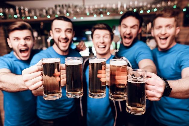 Grupo de aficionados al deporte bebiendo cerveza y celebrando.