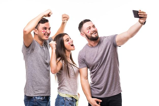 Grupo de aficionados al fútbol toman selfie equipo nacional de inglaterra sobre fondo blanco. concepto de aficionados al fútbol.
