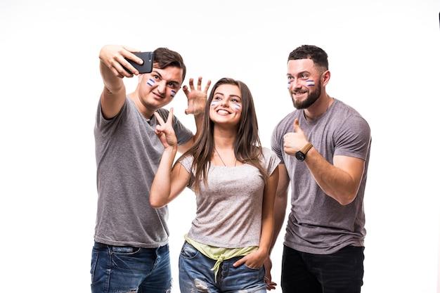Grupo de aficionados al fútbol se toman selfie mientras apoyan a la selección argentina sobre fondo blanco. concepto de aficionados al fútbol.