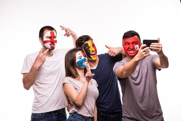 Grupo de aficionados apoyan a sus selecciones nacionales con caras pintadas. inglaterra, bélgica, túnez, panamá fans toman selfie en teléfono aislado sobre fondo blanco.