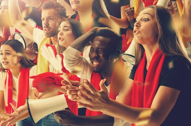 Grupo de aficionados felices están animando a la victoria de su equipo.