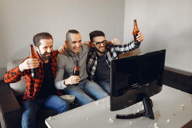 Grupo de aficionados está viendo fútbol en la televisión