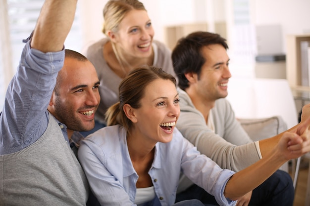 Grupo alegre de amigos que miran el partido de fútbol en la tv