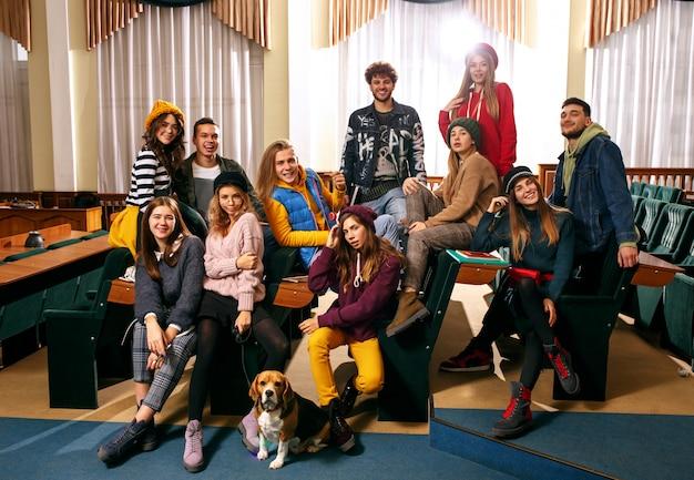 El grupo de alegres estudiantes felices sentados en una sala de conferencias antes de la lección