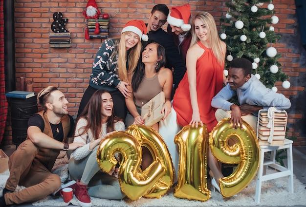 Grupo de alegres viejos amigos se comunican entre sí. se acerca el nuevo año 2019. celebra el año nuevo en un ambiente hogareño acogedor