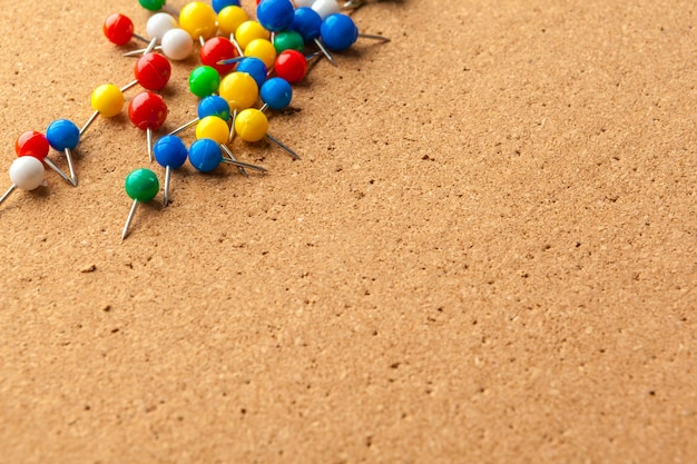 Grupo de alfileres de colores en el tablón de corcho