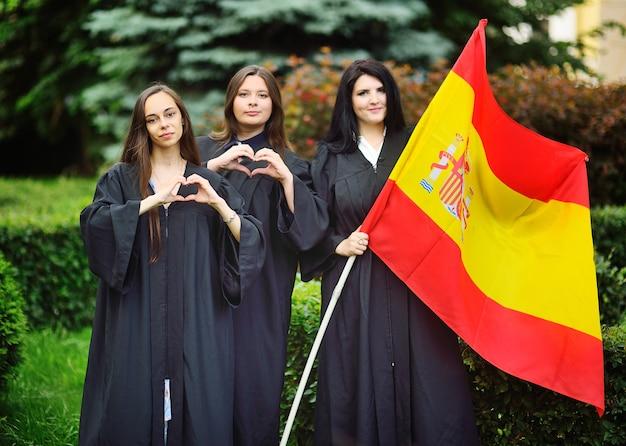 Un grupo de alumnos egresados de la facultad de lenguas extranjeras con túnicas sostienen la bandera de españa en sus manos