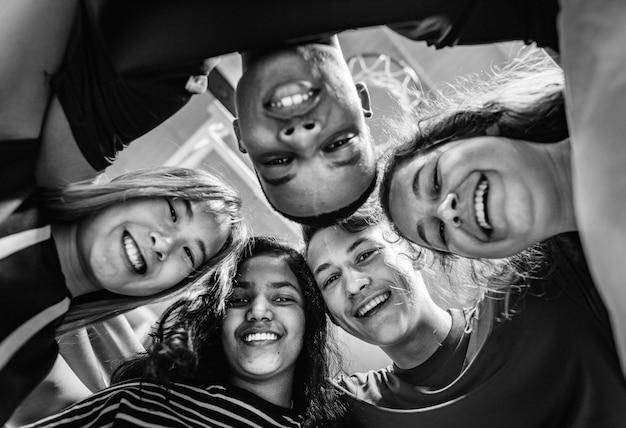 Grupo de amigos del adolescente en un concepto de trabajo en equipo y unidad de la cancha de baloncesto