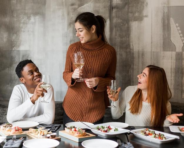 Grupo de amigos adultos cenando juntos