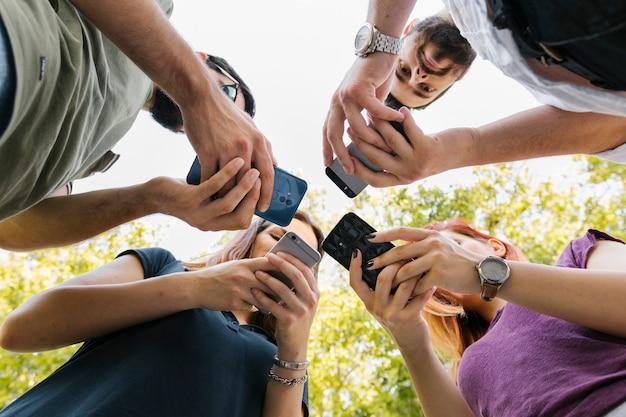 Grupo de amigos adultos de pie y mensajes de texto juntos