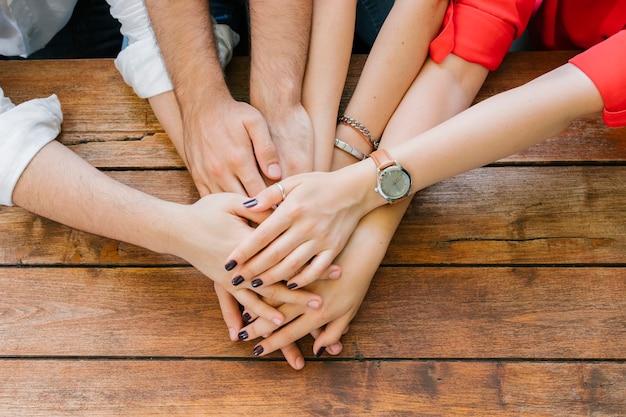 Grupo de amigos adultos poniendo las manos juntas en la mesa