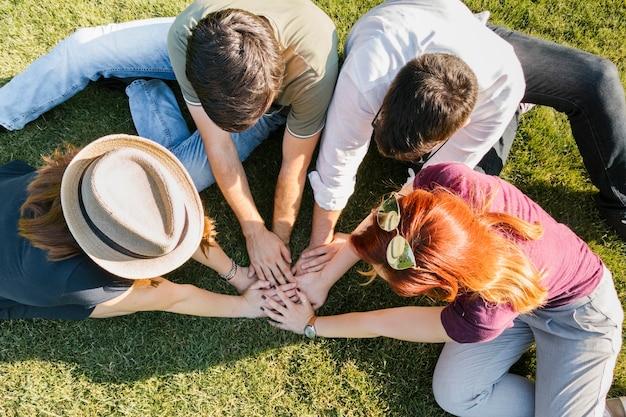 Grupo de amigos adultos poniendo las manos juntas