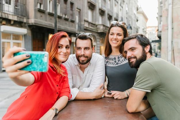 Grupo de amigos adultos sonrientes tomando selfie juntos